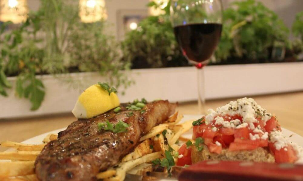 A plate of a steak on a bed of fries with a side salad and a glass of wine on the background